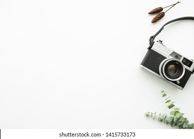 White minimal hipster photographer office desk table with retro film camera. Top view with copy space, flat lay.
