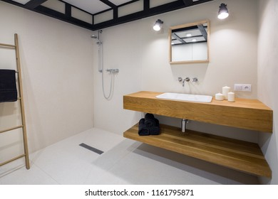 White minimalist bathroom with long, wooden countertop basin