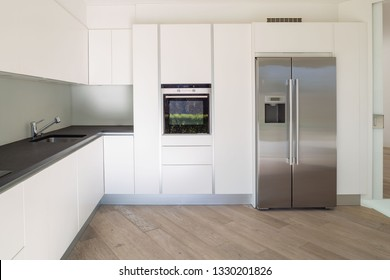 White minimalist modern kitchen, front view. Nobody inside