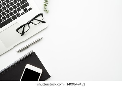 White minimalist office desk table with laptop computer, notebook with pen, smartphone and supplies. Top view with copy space, flat lay.