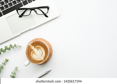 White minimalist office desk table with laptop computer, cup of latte cofee and supplies. Top view with copy space, flat lay, minimal style.