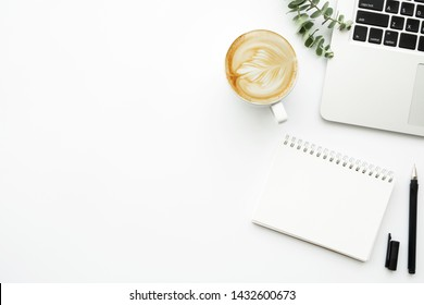 White minimalist office desk table with blank notebook page with pen, cup of latte coffee and laptop computer. Top view with copy space, flat lay.