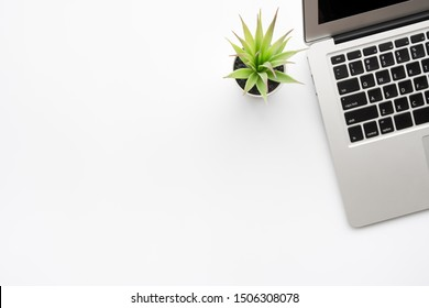 White minimalist office desk table with laptop computer and cactus pot. Top view with copy space, flat lay.