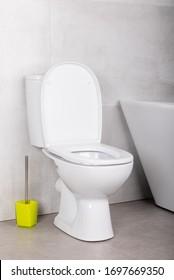 White minimalistic modern ceramic toilet bowl on the grey floor tile near the bath tube and yellow toilet brush