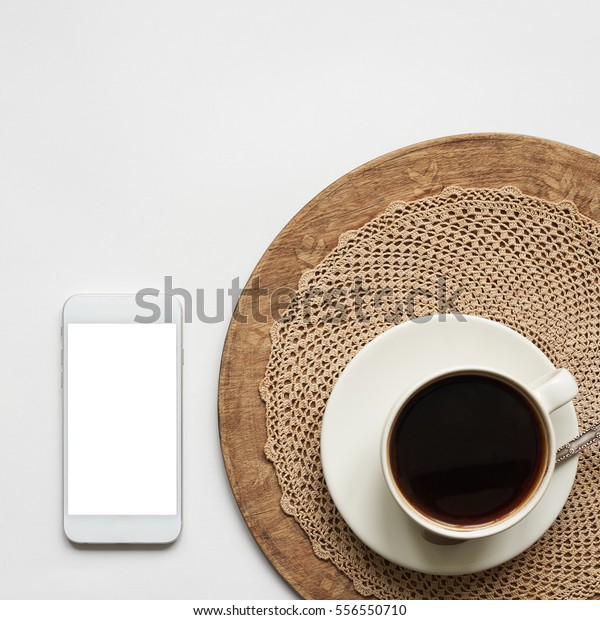 White mobile phone with blank copy space screen and cup of coffee on a stylish retro wooden tray, lace doily. Trendy vintage mock up with empty space for your promotional content.