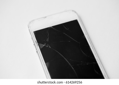 White mobile phone on a white background with a broken screen.