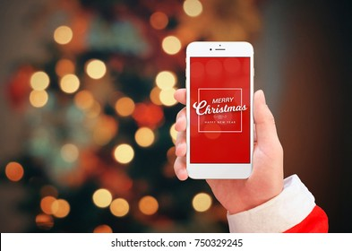 White mobile phone in Santa Claus hand close up. Merry Christmas greeting on phone display. Christmas bokeh lights in background.