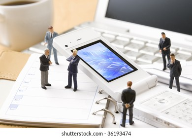 A white mobile phone surrounded by six models of  businessman