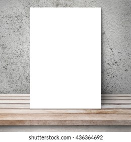 White mockup template paper on wood table is leaning on old grunge cement wall.