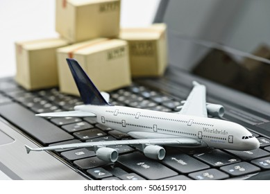 White model airplane lands on a laptop keyboard with boxes of goods behind. An idea of global things concerns aviation can be done online at hand ie. ticket booking, flight schedule tracking, shipping