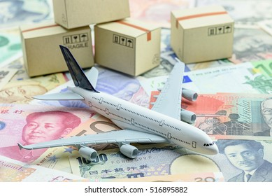White model airplane lands on banknotes from most famous countries around the world with boxes of goods behind. An idea of air freight transportation, global parcel forwarding, international shipping