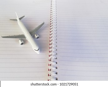White Model Jet Airplane on Notebook with Line. Copy Space for Text. Idea Concept for Study Education Abroad or Tour Trip Travel Planning on Holiday or Vacation.