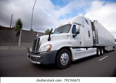 White modern American bonnet popular big rig semi truck for long haul delivery with reefer unit on refrigerator semi trailer running on the highway with concrete fence and cloudy sky
