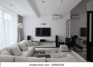 White modern apartments with air conditioning and TV and long-transparent curtains