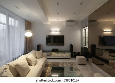 White modern apartments in the evening with air conditioning and TV and long-transparent curtains