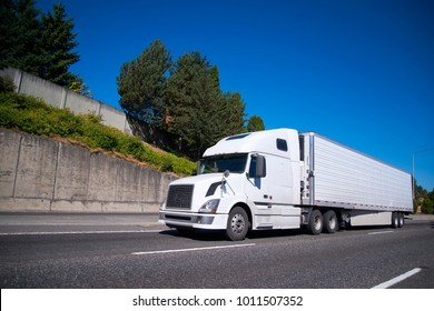 0408408792 White modern Big rig semi truck with reefer semi trailer equipped with  refrigeration unit going on