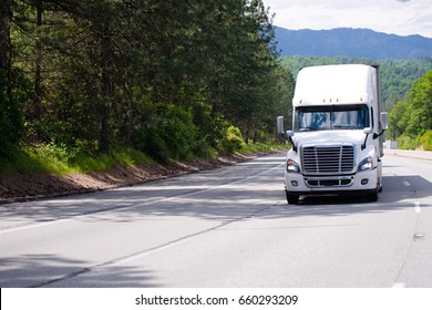 White modern big rig semi truck with chrome grille and dry van trailer driving by wide multi-line highway with green trees and shadow