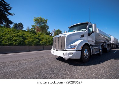 A white modern big rig semi truck tractor with a two tank semi trailers moves forward along a wide marked multi-lane highway framed along the sides of a rows of ever-green trees