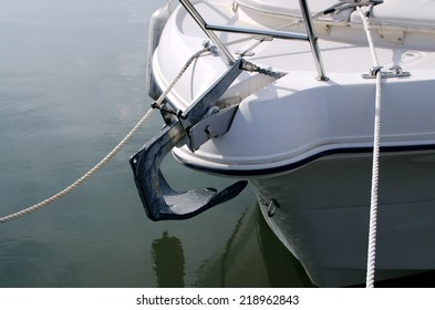 White modern boat with anchor on the dock.