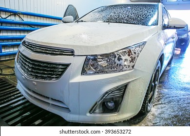 white modern car covered with foam in car wash