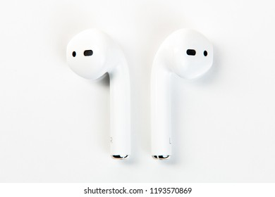 White modern earphones over white background. Close-up view. Handsfree.