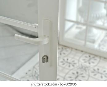 White modern glass door with door handle and lock. Concept of room interior design.