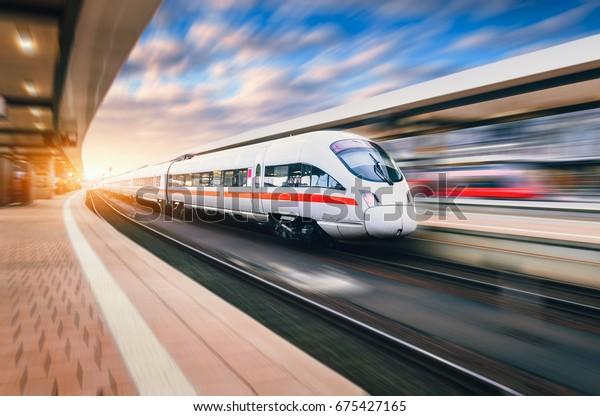 Weiße moderne Hochgeschwindigkeitszüge in Bewegung auf dem Bahnhof bei Sonnenuntergang. Zug auf Bahnschienen mit Bewegungsunschärfe in Europa am Abend. Bahnsteig. Industrielandschaft. Eisenbahntourismus
