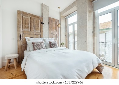 White modern interior design, apartment with double bed and wooden doors decor