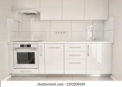 White modern kitchen in contemporary flat. Interior design of white modern kitchen. Minimalism in style.