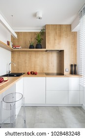 White, modern kitchen with wooden furniture and big window