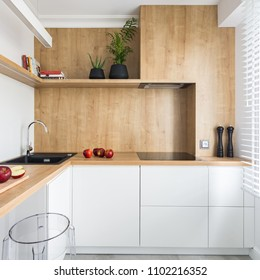 White, modern kitchen with wooden furniture and transparent stool