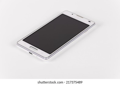 White modern smartphone with black screen lies on the surface, isolated on white background. Selective focus