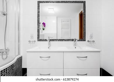 White, modern villa bathroom with basin cabinet, mirror and bathtub