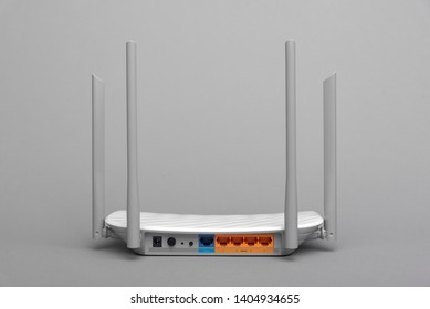 White modern Wi-Fi router with four antennas on a gray background.