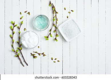 white moisturizer and blue cosmetic gel samples on white wood table
