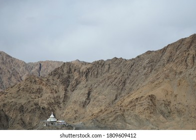 A white monastery building is dwarfed by the surrounding mountains in Ladakh, India. The mountain sides are barren. The sky is overcast.