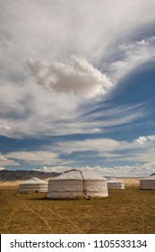 White Mongolian Yurts, Gers against a cloudy blue sky