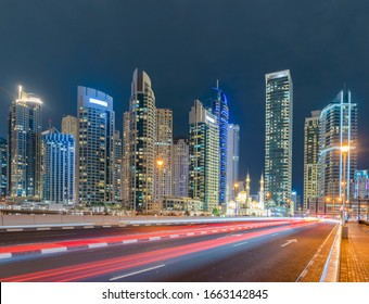 A white mosque near Dubai marina in downtown skyline, United Arab Emirates or UAE. Financial district and business area in smart urban city. Skyscraper and high-rise buildings at night.