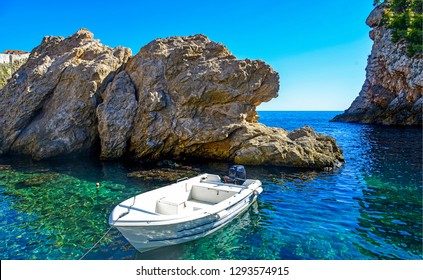 White motor boat in mountain sea bay scene. Motor boat sailing. Motor boat at sea rocks. White motorboat