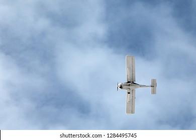 white motor plane flying against a blue sky