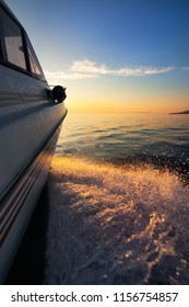 White motorboat moving fast to sunset