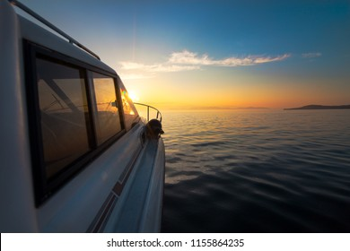 White motorboat moving to sunset