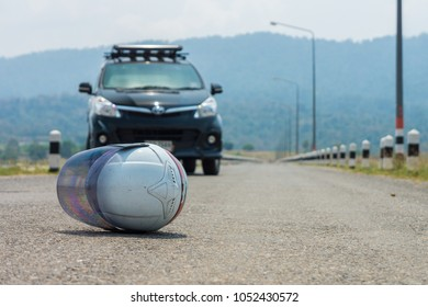 White motorcycle helmet on a road. Abstract of a road accident between black car and motorcycle.
