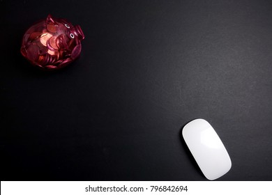 White mouse and red piggy bank over a black background.