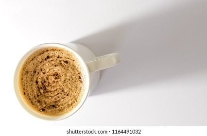 White Mug of Cappucino on White background. Mug of coffe on the lower left of the image with plenty of room for text.