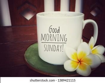 White mug of coffee with good morning sunday greeting on it and beautiful Balinese frangipani flowers arrangement. Happy Sunday! Have a relax sunday.