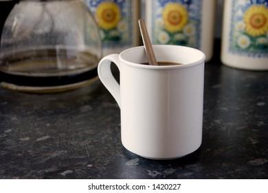 A white mug of coffee with a spoon