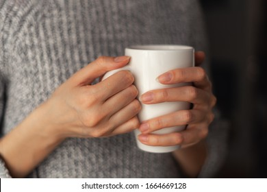 A white mug in the hands of a girl in a gray sweater. He warms his hands.