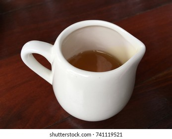 The white mug and honey keep on the table.