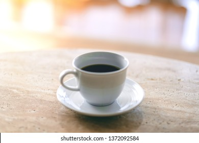 A white mug of hot coffee on the table